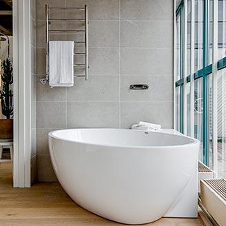 Badkar i ett hörn hos Hemmaplan badrum